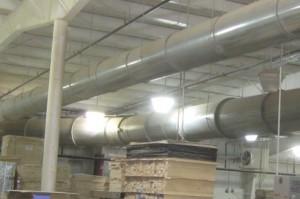 Egy ipari csarnokban lévő fatermékek felett húzódó cső képe